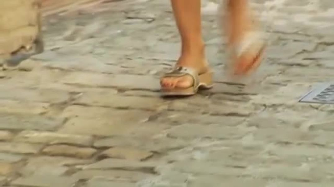 WOMEN IN SILVER SCHOLL SANDALS IN THE STREET