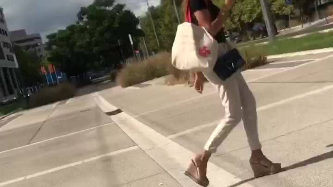 Candid sexy young woman walking in wedges