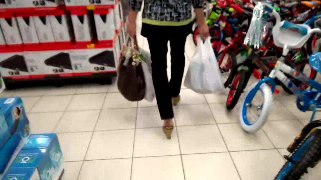 Asian walking through store in wedge mules