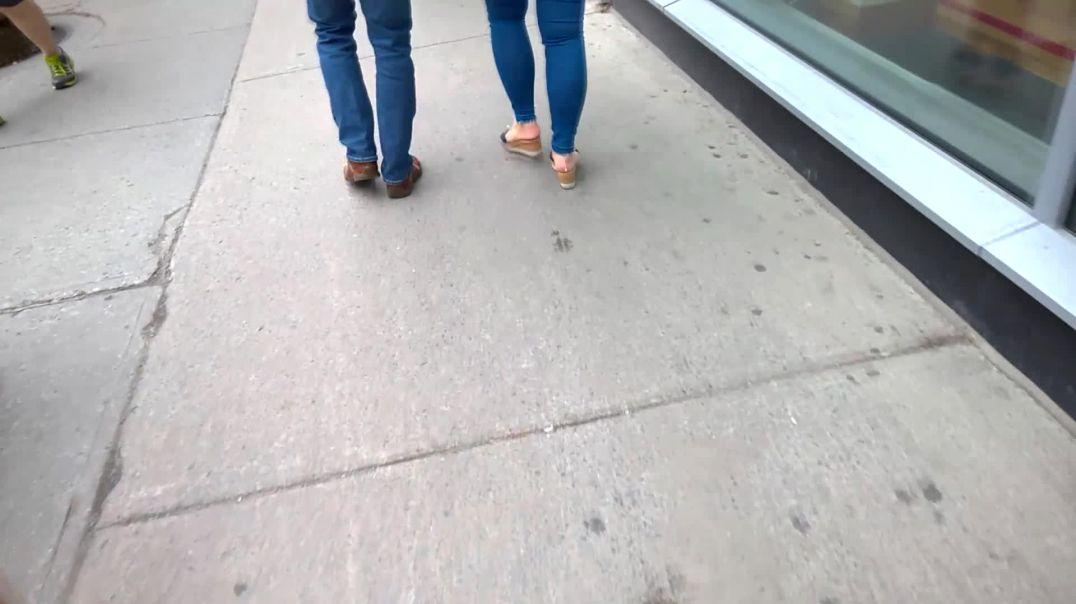 Redhead walking down the street in the city in wedge mules