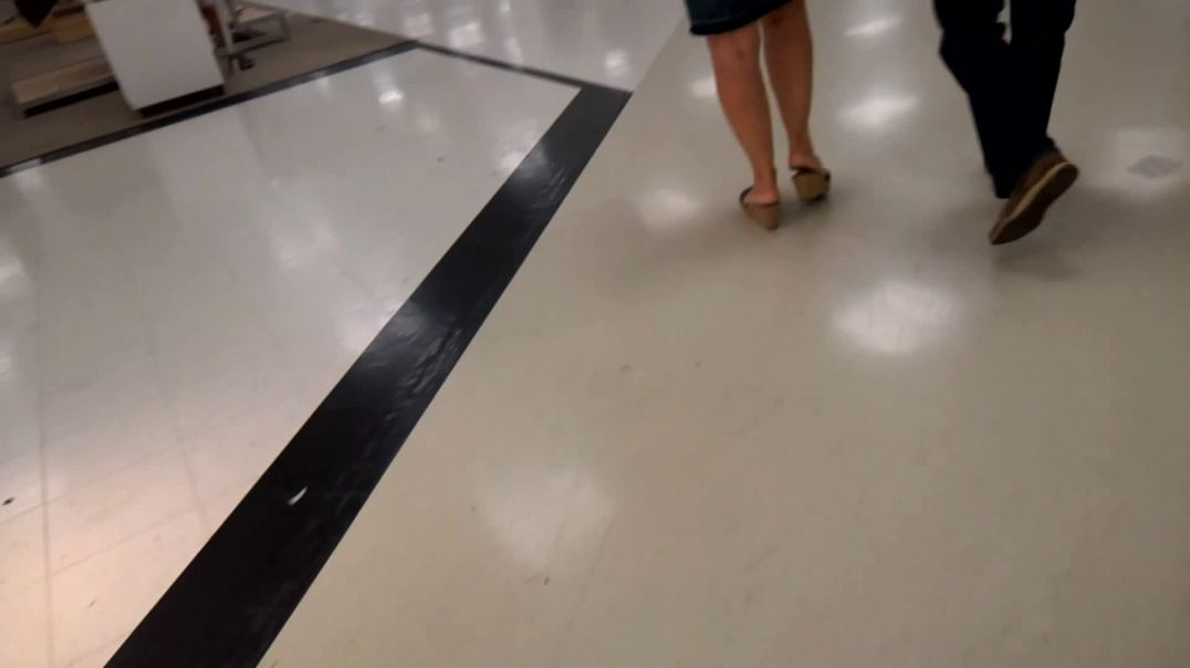 Woman in denim skirt walking in wedge mules