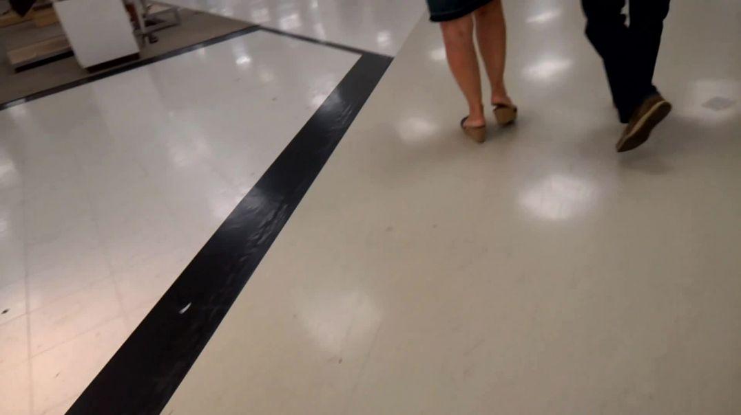 Woman in denim skirt walking in wedge mules