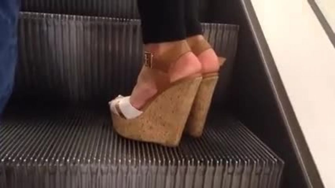 Girl in high heel platforms on escalator