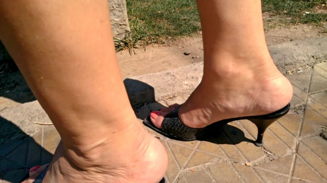 Sexy feet in black snake leather mules