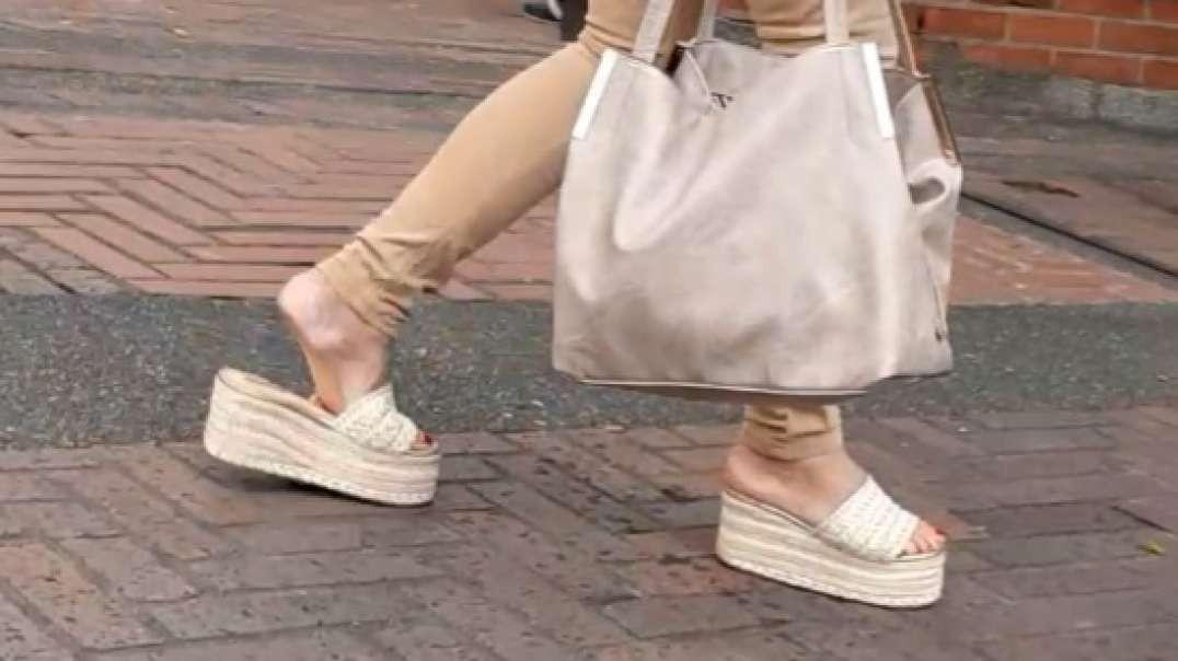 madura caminando en sandalias altas destalonadas